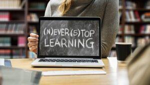 """Estudante a mostrar ecrã de computador que diz """"Never stop learning"""""""